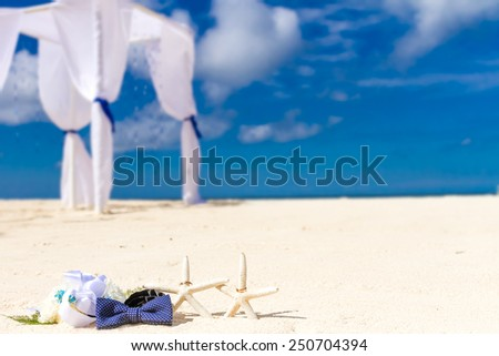 wedding rings on sand and starfish, outdoor beach wedding, wedding venue, details - stock photo