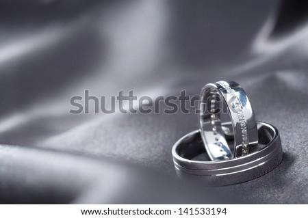 Wedding rings on satin - stock photo
