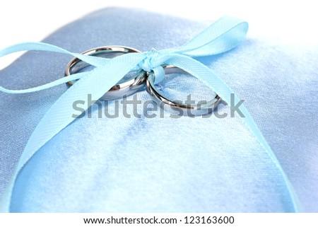 Wedding rings on satin pillow close-up - stock photo