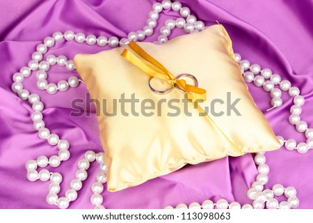 Wedding rings on satin pillow on purple cloth background