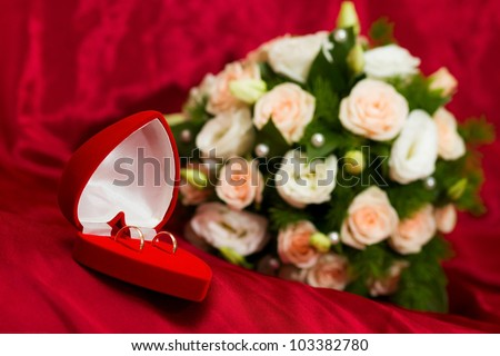 Wedding rings on the background of the wedding bouquet. The general background of red. - stock photo