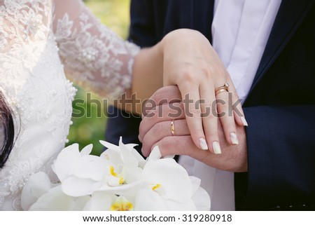 Wedding rings on the hands of newly-weds - stock photo