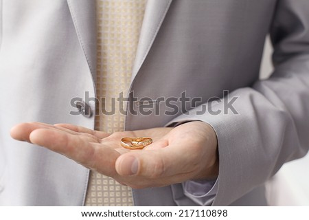 Wedding rings on the palm of the groom, marriage proposal - stock photo