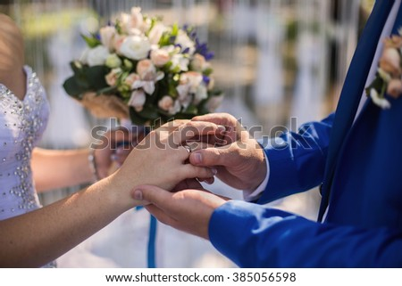 wedding rings on their hands, a ring on the finger, exchange rings, wedding ceremony - stock photo