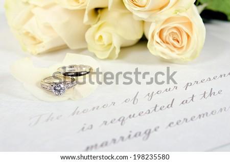 wedding rings on white rose petal with bridal bouquet and a traditional wedding invitation - stock photo