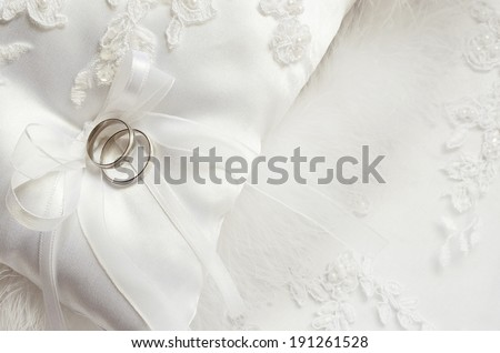 Wedding rings on white satin pillow  - stock photo