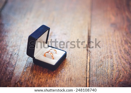 Wedding rings on wooded background - stock photo
