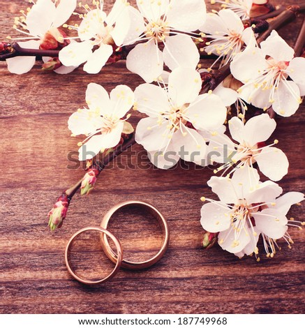 Wedding rings. Spring. Flowering branch with white delicate flowers on wooden surface. Declaration of love, two hearts, couple. Space for text  - stock photo