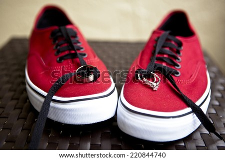 wedding rings tied to red casual shoes - stock photo