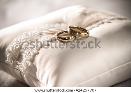 Wedding rings upon white pillow