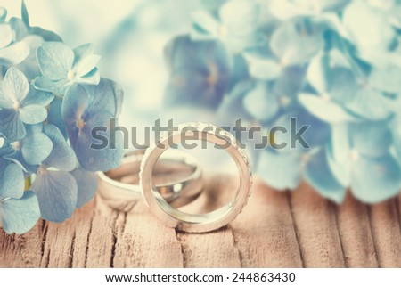 Wedding rings with blue hydrandea flowers. - stock photo