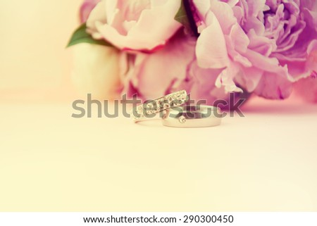 Wedding rings with bouquet of peonies. - stock photo