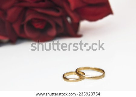 Wedding rings with red roses - stock photo