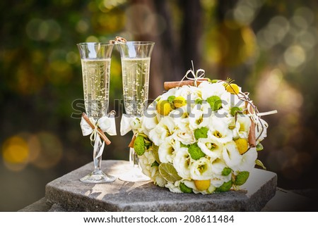 Wedding rings with roses and glasses of champagne - stock photo