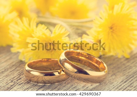Wedding rings with yellow flowers on wooden background