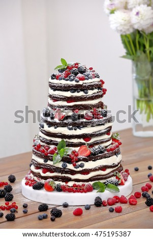 Wedding rustic naked cake with fruits on wooden background