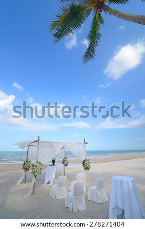 wedding setup on the beach, decorated with flowers - stock photo