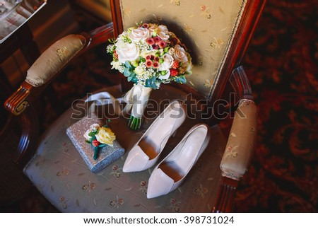 Wedding shoes and bouquet on a chair - stock photo