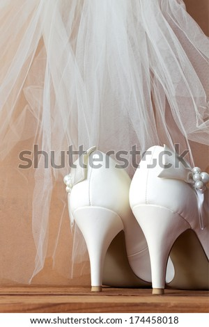 Wedding  shoes and veil. White wedding shoes and veil on the old wooden floor - stock photo