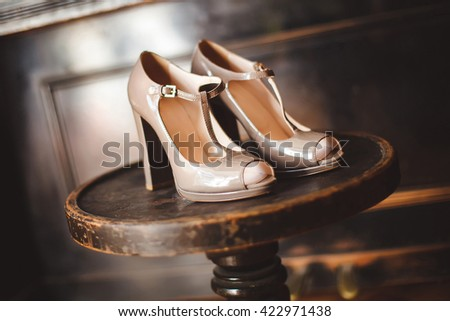 Wedding shoes at the hotel on a wooden chair.