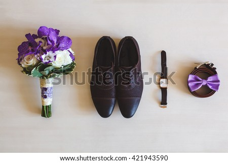 Wedding shoes, belts, watches and bouquet on a white surface. Accessories for the groom on the wedding day. - stock photo