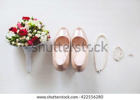 Wedding shoes cream color on a white table. Earrings. Bracelet. Necklace. The bride's bouquet.