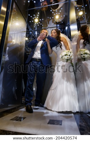Wedding shot of  bride and groom in lift - stock photo