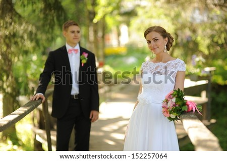 Wedding shot of bride and groom in park. Focus on bride