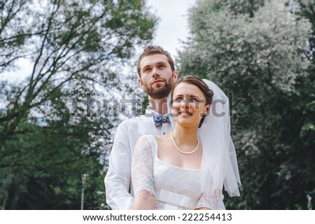 Wedding shot of bride and groom in park. hey kiss and hug each other