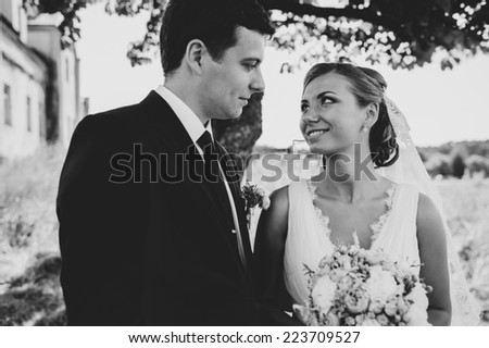 Wedding shot of bride and groom in park. summer nature outdoor. Beautiful bride and groom is enjoying his wedding day. They kiss and hug each other
