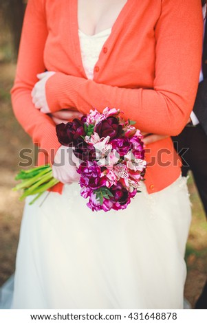 Wedding shot of bride and groom in park. Wedding couple just married with bridal bouquet. Stylish happy smiling newlyweds on outdoor wedding ceremony. Young couple in love outdoor.