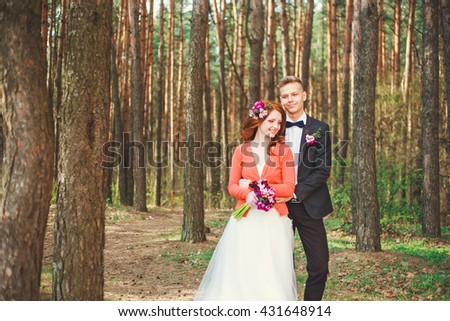 Wedding shot of bride and groom in park. Wedding couple just married with bridal bouquet. Stylish happy smiling newlyweds on outdoor wedding ceremony. Young couple in love outdoor.  - stock photo