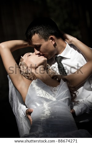 Wedding shot of bride and groom kissing against dark background - stock photo