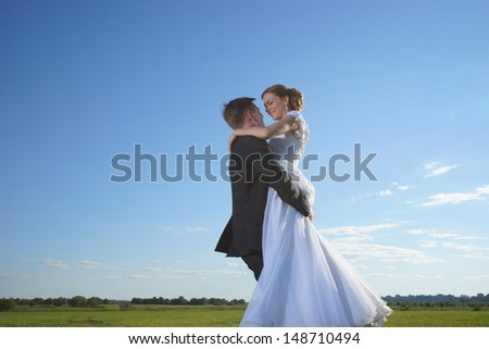 Wedding shot of bride and groom on field - stock photo