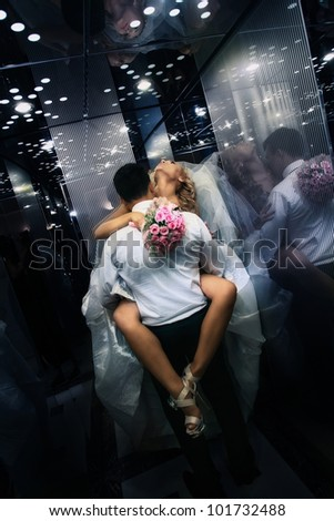 Wedding shot of sexy passion between bride and groom in lift - stock photo