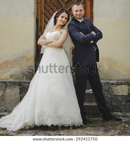 Wedding summer couple together posing against brick wall.
