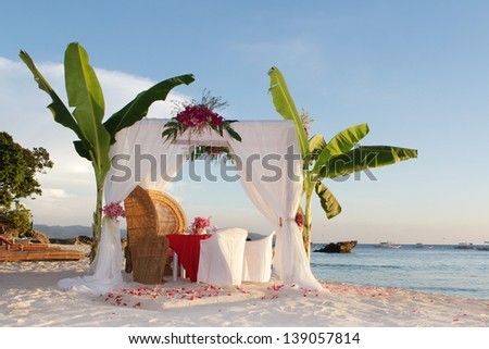 wedding table and set up with flowers on tropical beach - stock photo