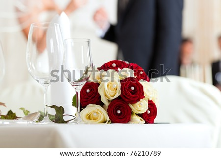 Wedding table at a wedding feast decorated with bridal bouquet - stock photo