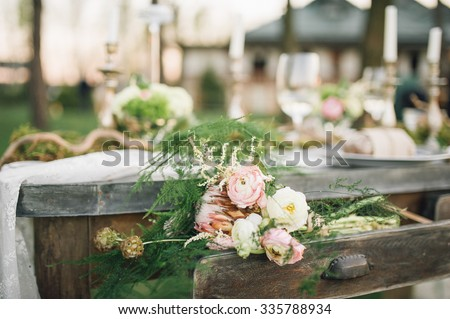 wedding table decorated by plates, knives and forks, candle, moss, greenery and bread