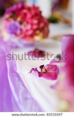 Wedding table decorated with a purple flowers - stock photo
