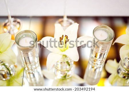 Wedding table decoration with flowers, candle and glassware