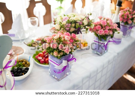 Wedding table served and decorated with many beautiful pink roses - stock photo