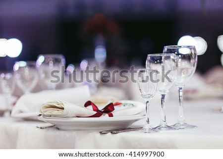 Wedding table set decorated with red ribbon - stock photo