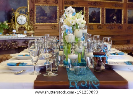 Wedding table setting arrangement in a historical room with antique furniture and decor.  - stock photo