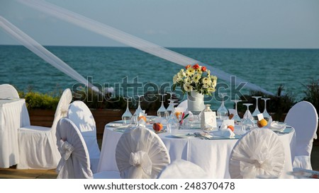 Wedding Table Setting. Luxury wedding dining table setting outdoors. Outdoor Table Setting at Wedding Reception by the Sea. - stock photo