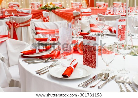 wedding tables set for fine dining or another catered event, red decoration - stock photo