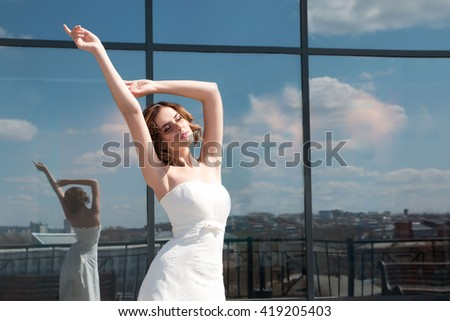 Wedding. the bride stands near the mirror wall. The mirrors reflect the clouds. the bride raised her hands up and closed his eyes
