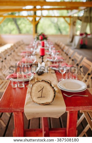 Wedding. The chairs and table for guests, decorated with candles and flowers, served  and covered with a tablecloth. Wooden sign with table number. Decoration with garland of light bulbs. - stock photo