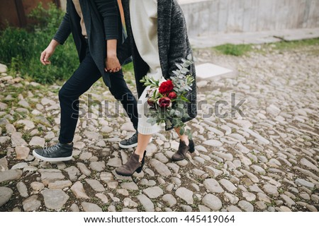 Wedding. The guy and the girl go on the stone road, a girl holding a bouquet of red, white flowers and greenery