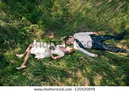 wedding theme, beautiful wife and husband are on the green grass - stock photo